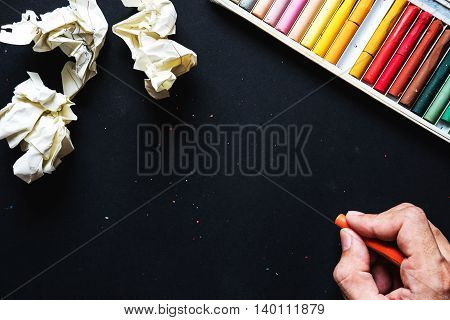 Hand hold orange crayon color, drawing on blackboard or black paper and crumpled paper ball, with copy space