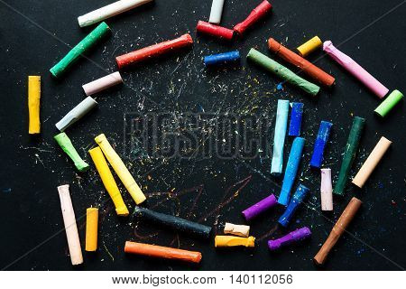 Colorful pastel crayon oil colors on chalkboard or black paper, with copy space