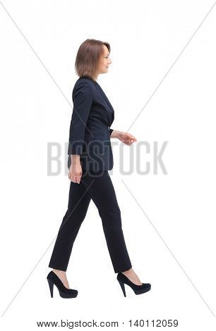 Full-length profile of walking businesswoman, isolated on white