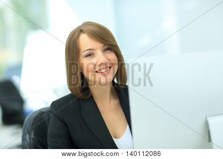Beautiful business woman dreaming while working on computer