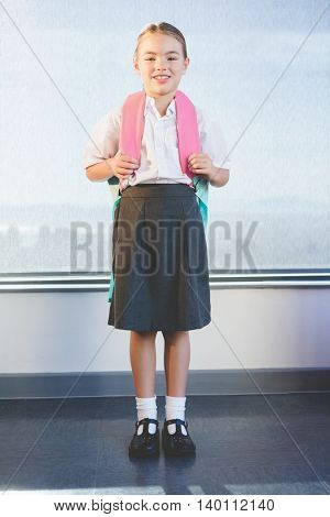 Portrait of happy schoolkid standing in classroom at school
