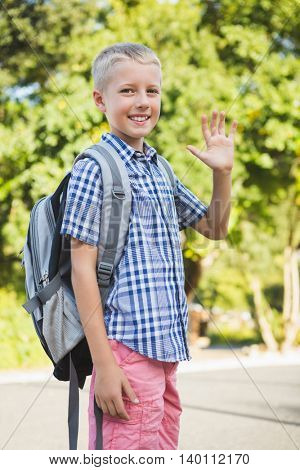 Portrait of happy schoolkid waving hand in campus