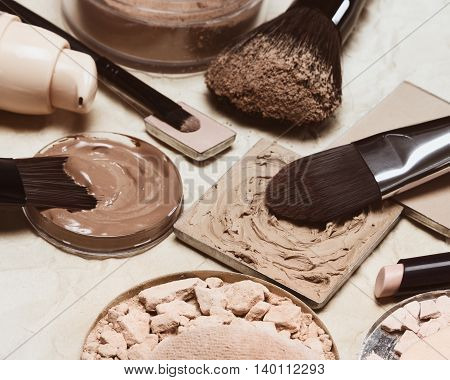 Stick concealer, correcting cosmetic powders, cream-to-powder and liquid foundation on crumpled aged paper. Makeup products to even out skin tone and complexion. Retro style processing