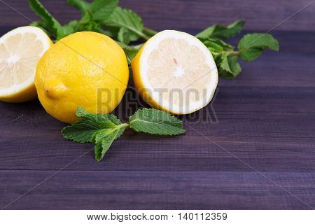 Ripe lemon with mint on a dark background. Space for text