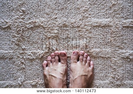 Feet standing on beige carpet, with copy space