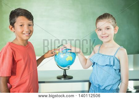 Portrait of schoolkids studying globe in classroom at school