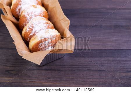 German donuts - delicious berliner with jam and icing sugar in a box on a dark wooden table. Space for text