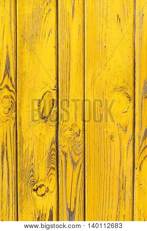 Vertical background of the old wooden planks with bright yellow paint