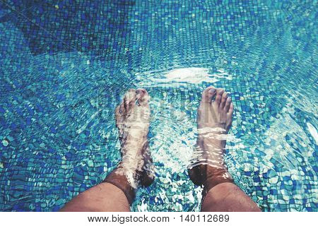 Male feet with skin tan, dipping in swimming pool