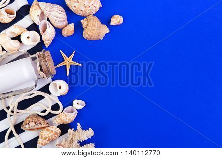 Marine items - seashells starfish coral and bottle with note on a blue background. Top view with copyspace.