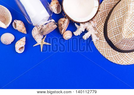 Holiday marine items - seashells starfish coral bottle with note coconut and straw hat on a blue background. Top view with copyspace.