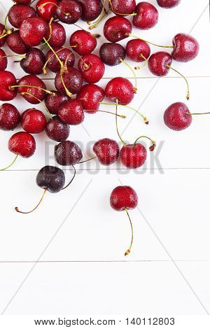 Red cherries with water drops on a white table. Space for text