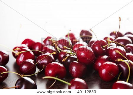 Red cherries with water drops on a dark background. Space for text