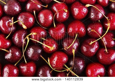 Background of red cherries with water drops