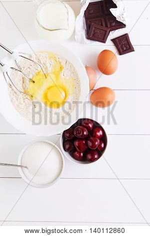 Ingredients for the pie - cherry flour eggs sugar milk and chocolate on a white wooden table