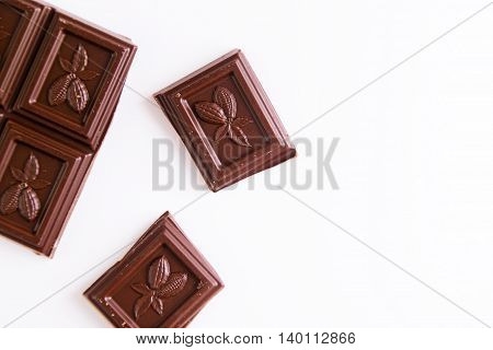 Broken dark chocolate bar on a white background. Space for text