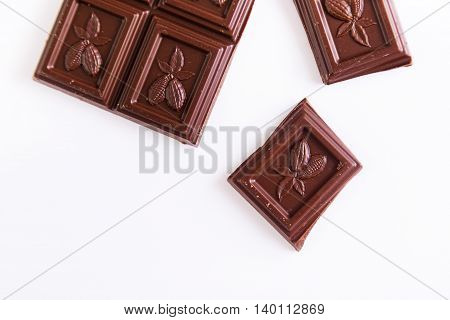 Broken dark chocolate bar on a white background. Top view with copyspace