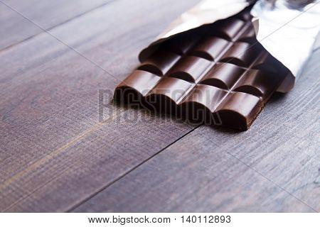 Dark chocolate bar on a dark wooden background. Space for text