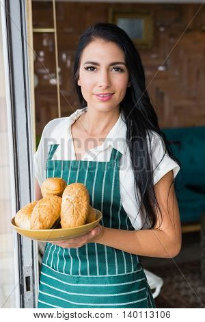 Portrait of waitress holding bowl with bread in cafeteria