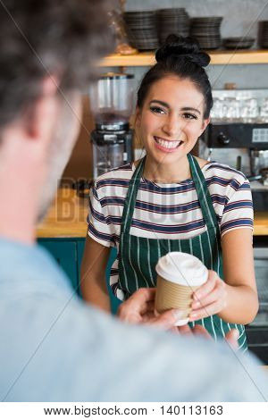 Waitress giving cup of coffee to customer in cafeteria