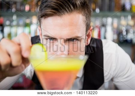 Close-up of waiter decorating cocktail with lime at bar counter in restaurant