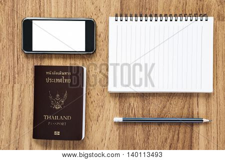 Blank notebook and mobile phone with Thai passport on wooden desk