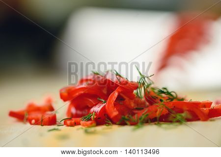 Cutting chili pepper with knife on wooden surface