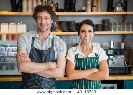 Portrait of waiter and waitress with arms crossed in cafeteria