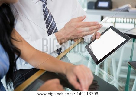 Mid section of businessman discussing with colleague over digital tablet in office