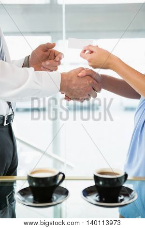 Mid section of businessman shaking hands and giving business card to colleague in office