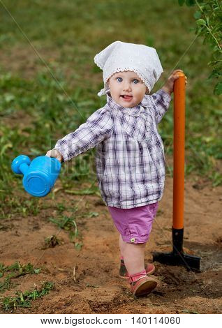 photo of little funny boy with shovel in garden