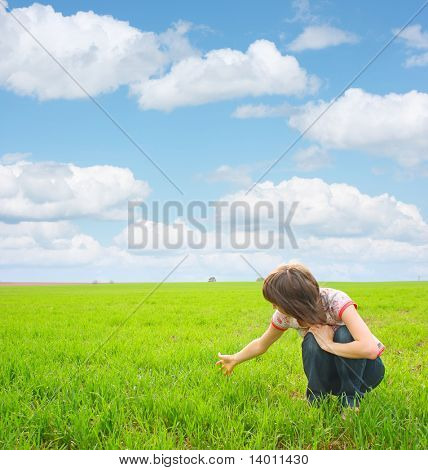 Young woman sitting on meadow with green grass under blue sky