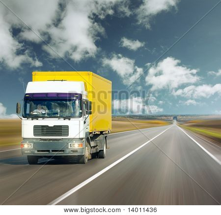 Yellow truck on road under blue sky