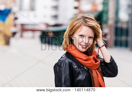 Young beautiful blonde woman walking on autumn street