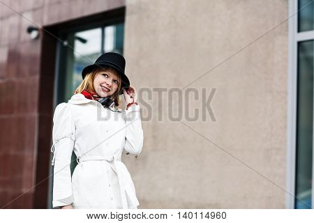 Beautiful young woman in white coat climbing stairs in business building