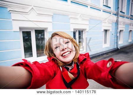 Smiling young girl making selfie in the city
