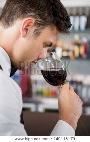 Close-up of waiter smelling a glass of wine in restaurant