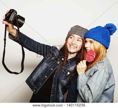 Happy girls friends taking some pictures, over grey background