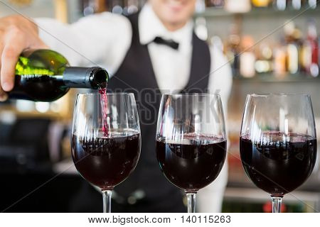 Close-up of waiter pouring wine into glasses in restaurant