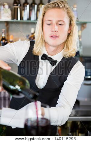 Waiter pouring wine into glass in restaurant