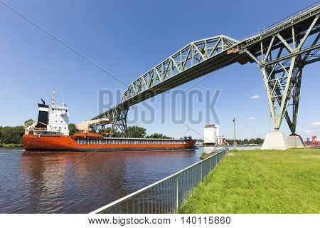 Freight ship passing historic Hochdonn railway bridge on Kiel Canal