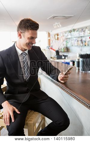 Businessman text messaging on mobile phone in restaurant