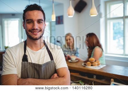 Portrait of happy young male barista with arms crossed at coffee shop