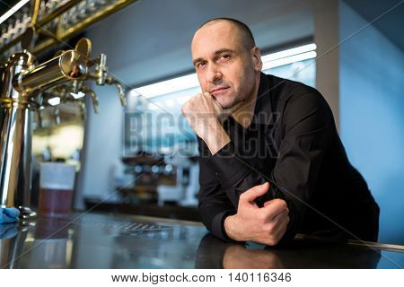Portrait of bar tender leaning at bar counter