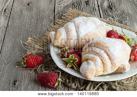 Croissants and fresh raspberries on dessert plate on gray wooden table.