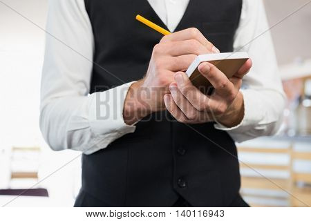 Mid section of waiter writing order on notepad in restaurant