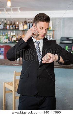Businessman checking time while talking on the mobile phone in the restaurant