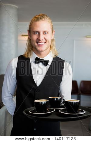 Portrait of waiter holding a tray with coffee cups in restaurant