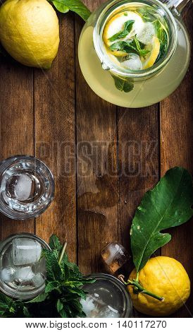 Jug full of homemade lemonade with mint, slices of lemon and ice cubes, served with fresh lemons and mint over wooden background, top view, vertical composition, copy space