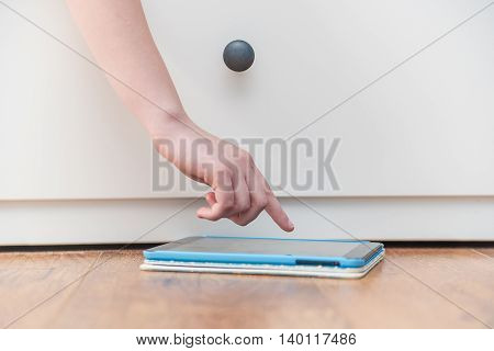 Close-up photography of teenage girl's hand touching tablet computer